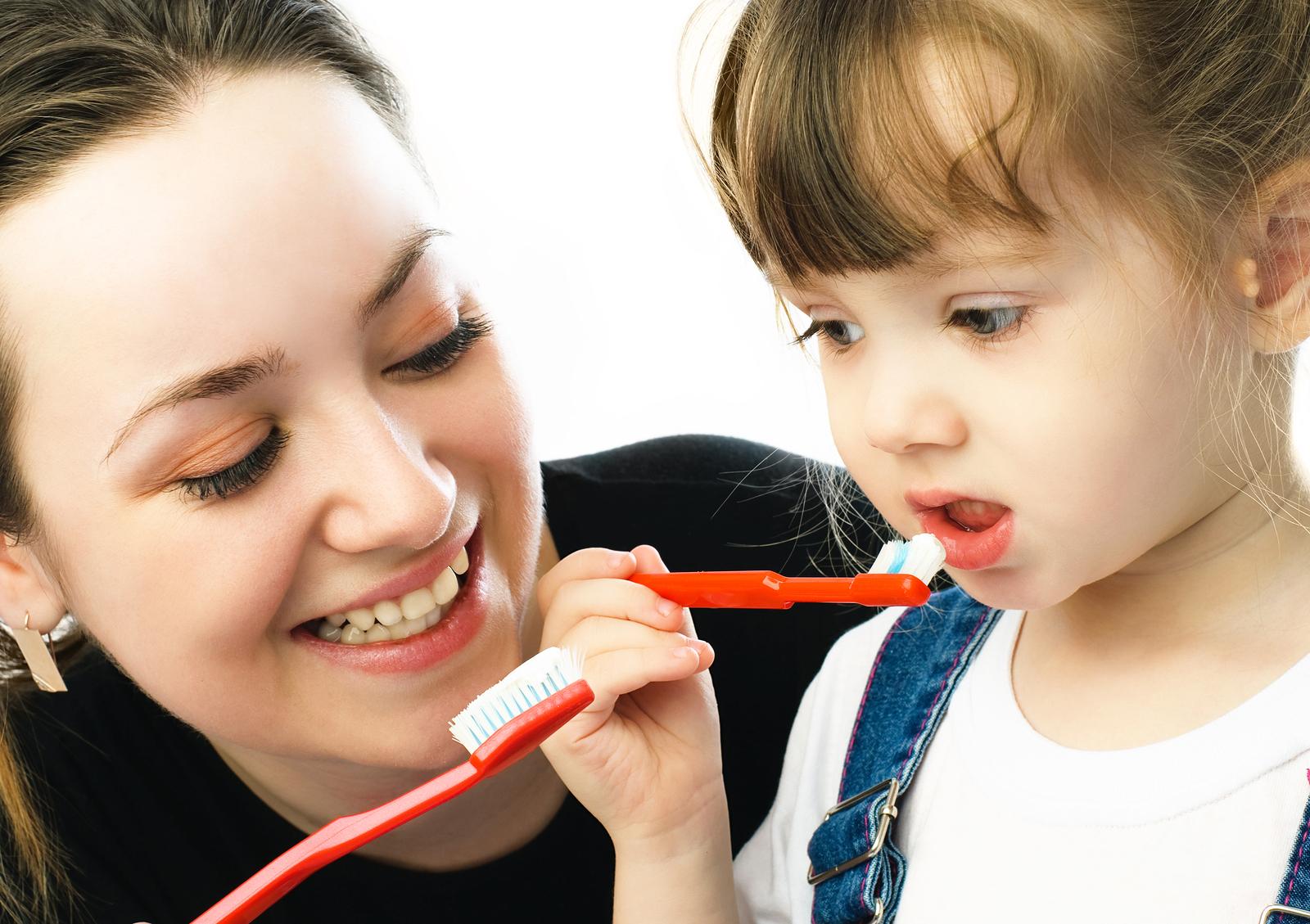 young beautiful mother teaching her daughter brushing teeth